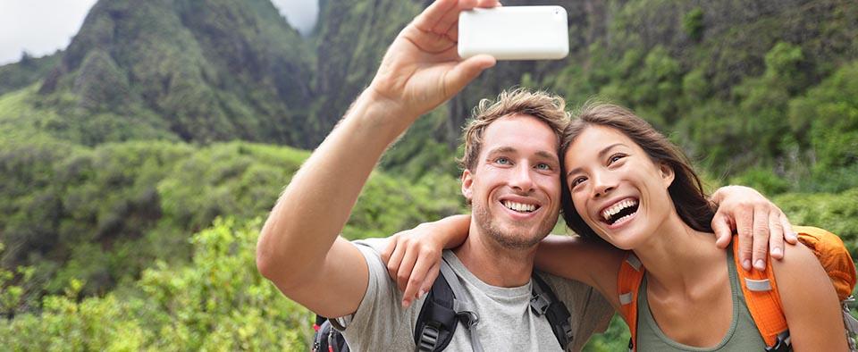 Couple taking selfie photo with smart phone hiking on Hawaii. Wo